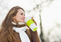 Woman drinking hot beverage in winter park Stock Photo