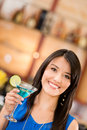 Woman drinking a martini at the bar and smiling Stock Photography