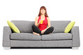 Woman drinking an orange juice seated on sofa isolated white background Stock Photo