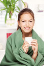 Woman drinking tea  at home covered with blanket Royalty Free Stock Image