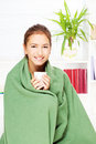 Woman drinking tea  at home covered with blanket Royalty Free Stock Photos