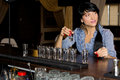 Woman drinking vodka shots at a bar attractive young sitting with long line of shot glasses i front of her as she downs them Royalty Free Stock Photos