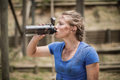 Woman drinking water from bottle during obstacle course Royalty Free Stock Photo