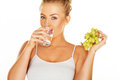 Woman drinking water and eating grapes close up of an attractive young blond a glass of fresh a bunch of delicious juicy green Stock Photo