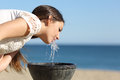 Woman drinking water from a fountain thirsty on the beach in sunny day Stock Photo
