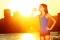 Woman drinking water after running female athlete enjoying sun and drink from bottle exercising outdoor in sunshine Royalty Free Stock Photos