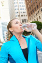 Woman drinking water whilst running along busy urban street Stock Images