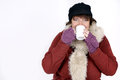 Woman drinking in winterclothes hot beverage over white background Stock Photo