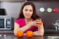 Woman drinks fresh juice young at domestic cooking Royalty Free Stock Images