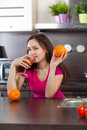 Woman drinks fresh juice young at domestic cooking Stock Image
