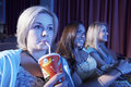 Woman drinks soft drink with friends watching movie in theatre closeup of young women drinking the Stock Image