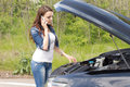 Woman driver calling for breakdown assistance beautiful young as she stands in front of her car with the bonnet up looking at the Royalty Free Stock Photos