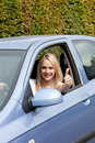 Woman driver giving a thumbs up beautiful young of appreciation and success as she tries out her new car Royalty Free Stock Photos