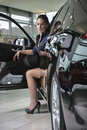 Woman driver with her new car gorgeous female wearing high heel shoes is sitting in fancy which door is open auto salon background Royalty Free Stock Image