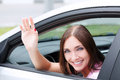 Woman driver smiling and greeting you by hand Stock Photos