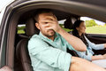 Woman driving car and man covering face with palm Royalty Free Stock Photo