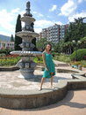The woman at the dry fountain in a bright sunny day green dress standing of summer Royalty Free Stock Photography