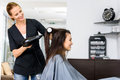 Woman drying hair of her client in salon Royalty Free Stock Photo