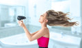 Woman drying hair young blonde her long with electric fan Royalty Free Stock Images