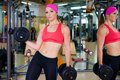 Woman with dumbbells beautiful sport background gym Stock Photos