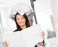 Woman dying her hair at the beauty salon and reading the newspaper Royalty Free Stock Photo