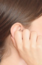 Woman ear young holding her Stock Photography