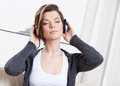 Woman in earphones listens to music Royalty Free Stock Image