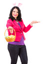 Woman with easter basket welcome bunny ears holding eggs and make presentation isolated on white background Royalty Free Stock Images