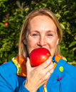 Woman eating and apple in an orchard middle aged biting into a freshly picked red Stock Photos