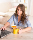 Woman eating breakfast at home beautiful young cornflakes and drinking coffe while working with laptop Stock Image