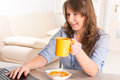 Woman eating breakfast at home beautiful young cornflakes and drinking coffe while working with laptop Royalty Free Stock Photography