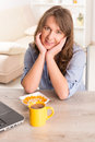 Woman eating breakfast at home beautiful young cornflakes and drinking coffe while working with laptop Royalty Free Stock Images
