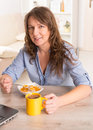 Woman eating breakfast at home beautiful young cornflakes and drinking coffe while working with laptop Stock Photo
