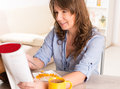 Woman eating breakfast at home beautiful young cornflakes and reading newspaper Royalty Free Stock Image