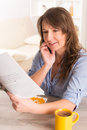 Woman eating breakfast at home beautiful young cornflakes and reading newspaper Stock Image