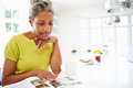 Woman eating breakfast and reading magazine in kitchen Stock Photo
