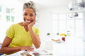Woman eating breakfast and reading magazine in kitchen smiling to camera Royalty Free Stock Image