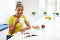 Woman eating breakfast and reading magazine whilst holding hot drink smiling to camera Royalty Free Stock Photo