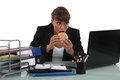 Woman eating a burger at her desk Royalty Free Stock Photography