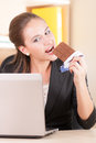 Woman eating chocolade in office happy Stock Photos