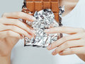 Woman eating chocolate, close up hands with manicure french nails holding candy, beautiful fingers Royalty Free Stock Photo