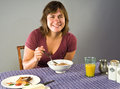 Woman eating gluten free breakfast young s enjoys flax cereal and toast for Stock Photography