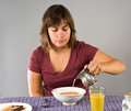 Woman eating gluten free breakfast young s pouring milk onto her flax cereal part of a Royalty Free Stock Photo