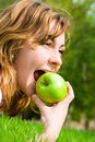 Woman eating green apple on the summer glade Royalty Free Stock Photo