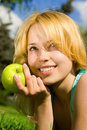Woman eating green appleon the summer glade Royalty Free Stock Images