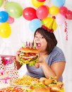 Woman eating hamburger at birthday. Stock Photos