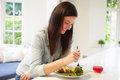 Woman Eating Healthy Meal In Kitchen Royalty Free Stock Photo