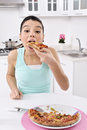 Woman eating pizza at kitchen girl smiling looking at camera portrait of young asian model Royalty Free Stock Images