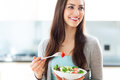 Woman eating salad young in modern kitchen Stock Photo