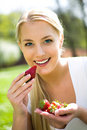 Woman eating strawberries Stock Image